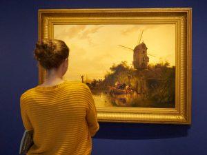 vrouw kijkt naar schilderij Waterland met molen van Wijnand Nuijen