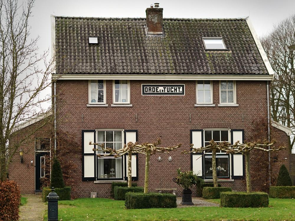 Afbeelding: huis in Veenhuizen, met daarop de tekst: orde en tucht
